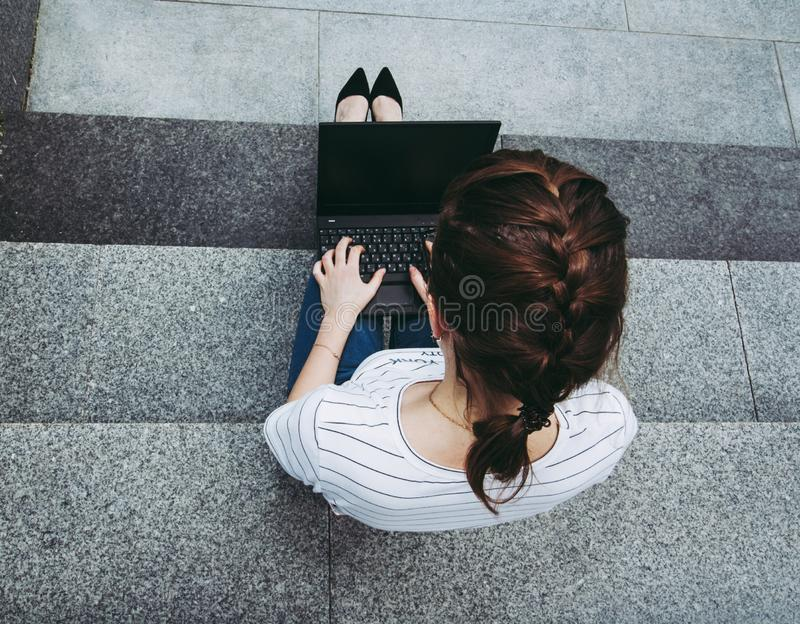 girl with notebook sitting on the gray steps royalty free stock photo