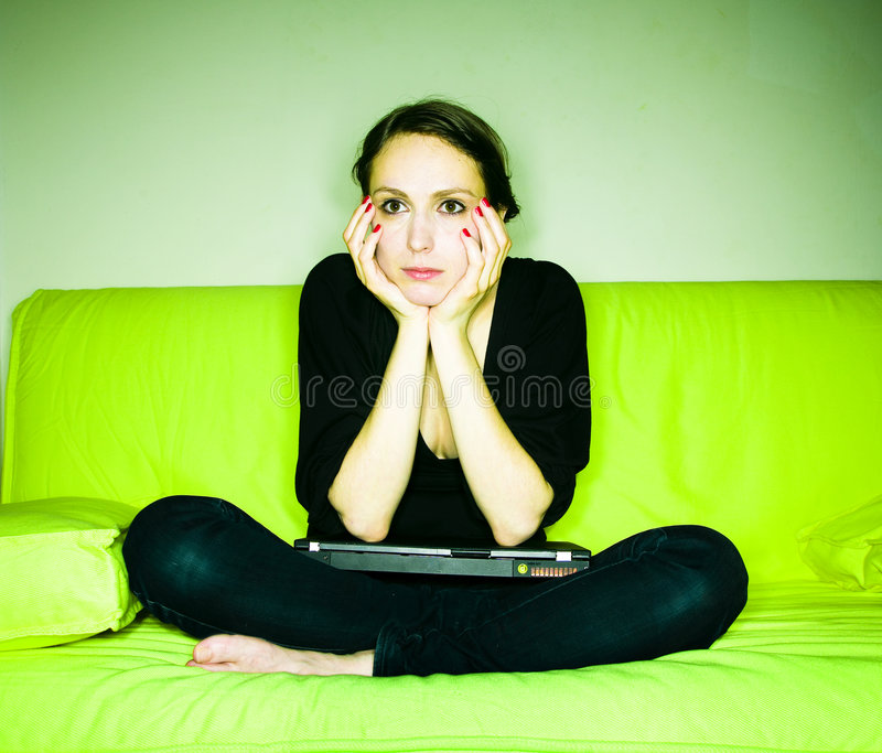Woman with laptop on sofa royalty free stock photography