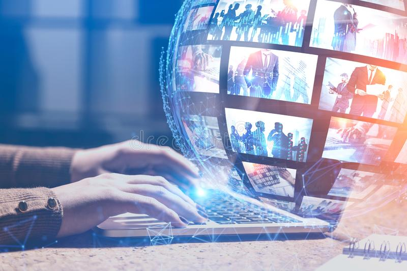 Woman with laptop using video streaming technology. Woman hands typing on laptop with double exposure of futuristic video streaming interface and planet hologram royalty free stock images