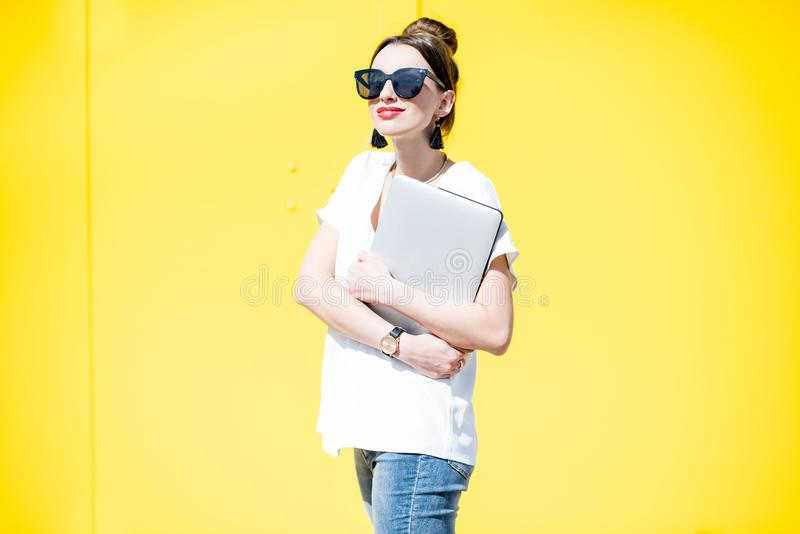 Woman33 with laptop on the yellow wall background royalty free stock images