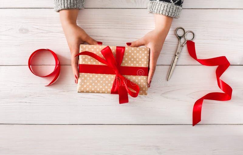 Woman& x27; las manos de s dan el regalo de la Navidad en la actual caja imagenes de archivo