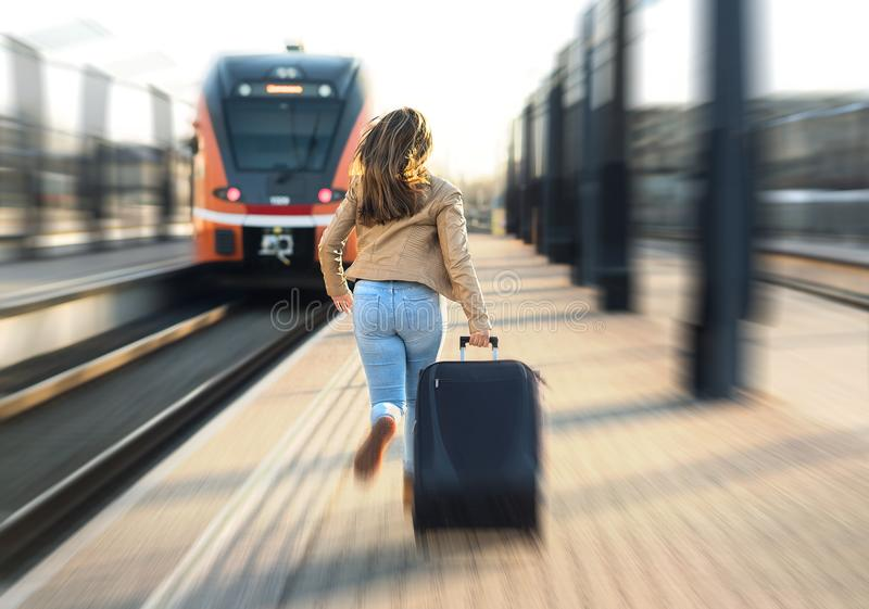 Woman late from train. Tourist running and chasing. stock photography