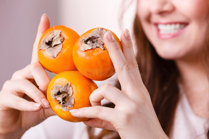 Cheerful woman holds persimmon kaki fruits stock photos