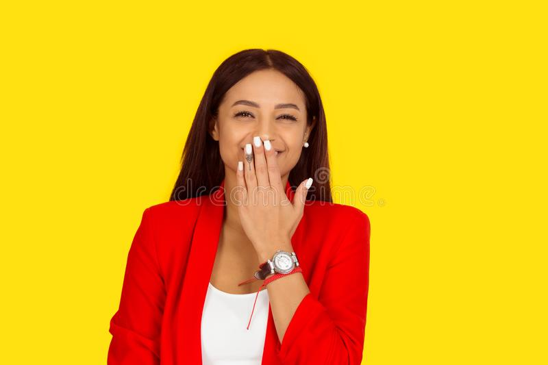 Woman laughing with hand covering her mouth, looking at you camera royalty free stock photography