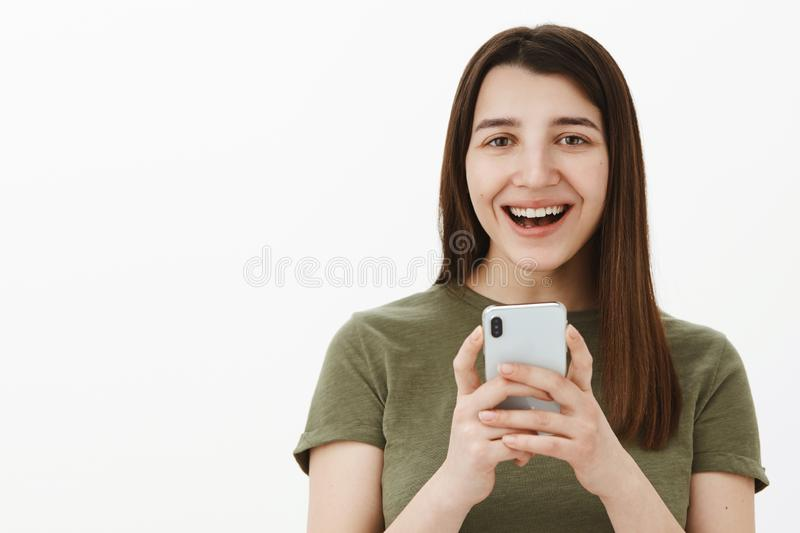 Woman laughing over funny photo of you taken via smartphone holding mobile phone in hands smiling broadly amused and. Carefree at camera having fun as posing stock photo