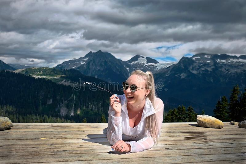 Woman laughing. Young lady hiker taking rest in campground royalty free stock image