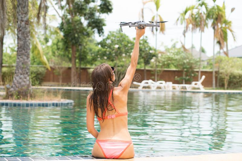 A woman launches a drone for flight, with which you can take photos and video filming stock photos