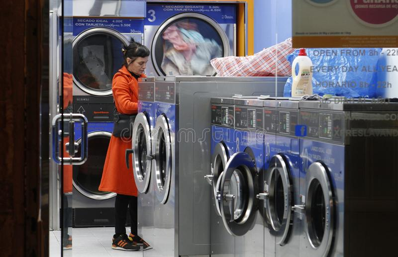 Woman in a laundromat waiting for her clothes. Barcelona, Spain- November 09, 2016. The self-service laundries are ready to take over the domestic washing