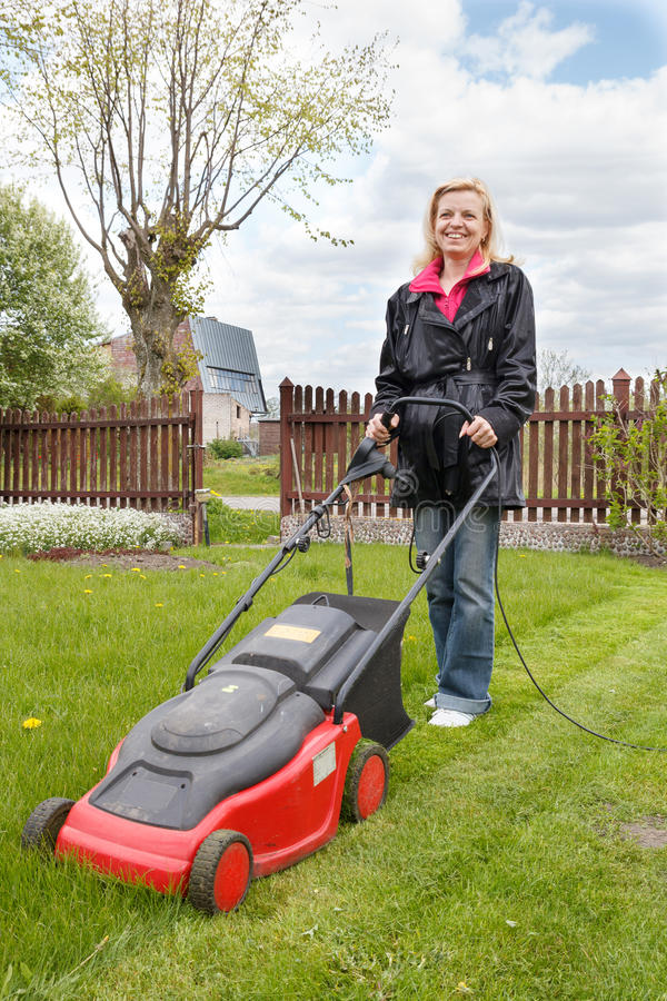 Woman with lawn mower stock photo