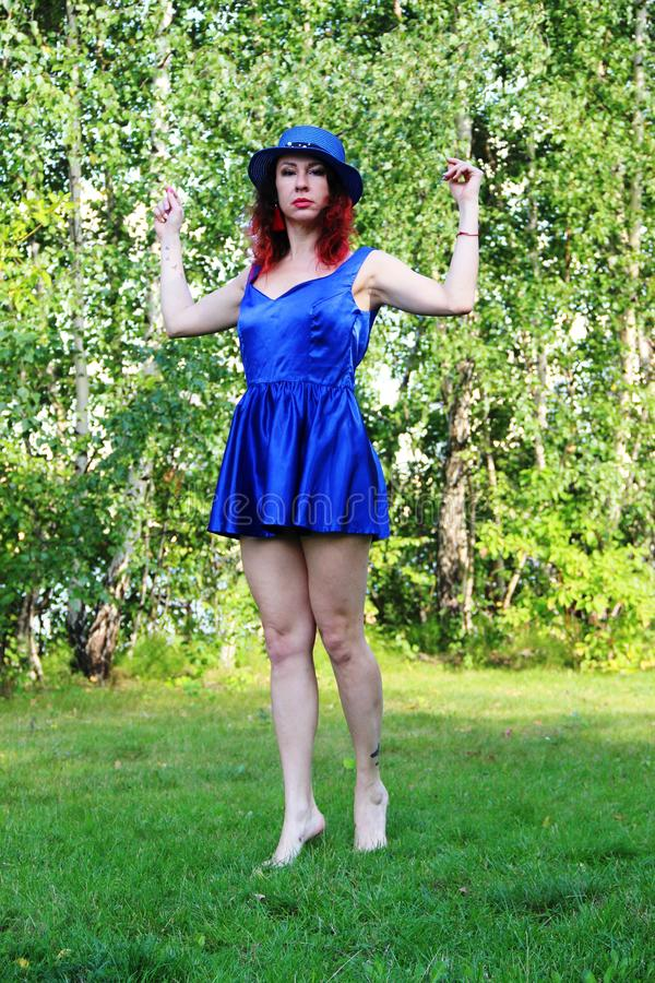 Woman on the lawn with red curly hair in a blue hat and short blue mini dress. Hands raised up and bent at the elbows. royalty free stock images