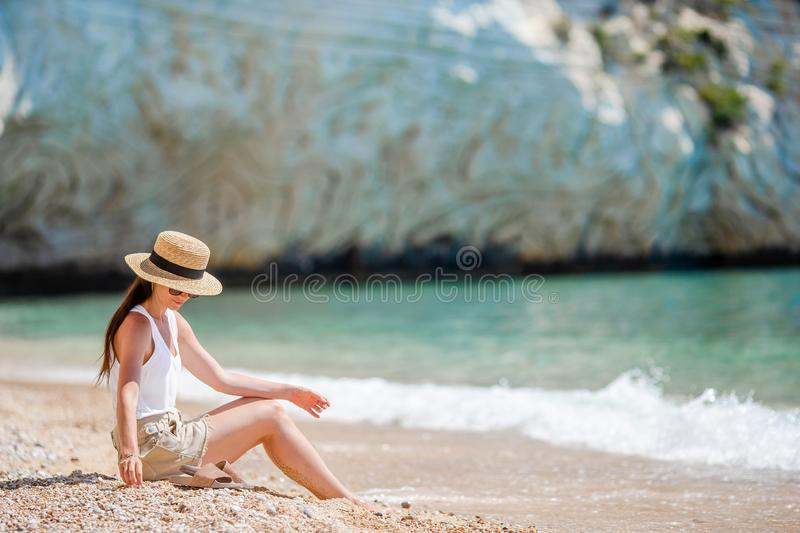 Woman laying on the beach enjoying summer holidays looking at the sea. Young beautiful woman on empty beach royalty free stock photography