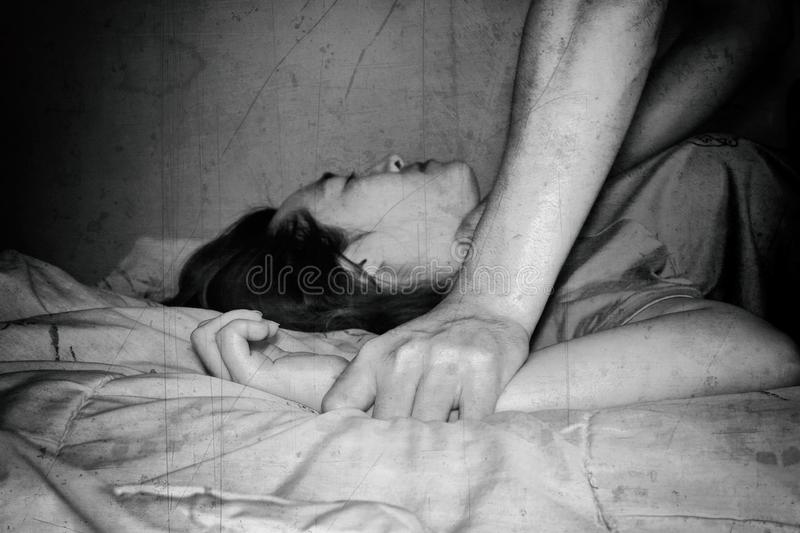 Woman laying on bed with fear, violence , sexual abuse, human trafficking stock photo