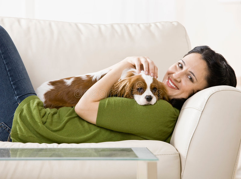Woman laying on couch with puppy royalty free stock photography
