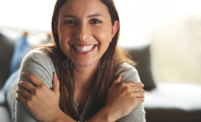 Woman laying on couch smiling widely. stock photo