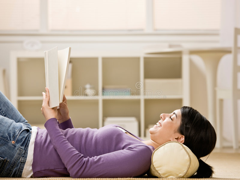 Woman laying on floor enjoying reading a book royalty free stock images