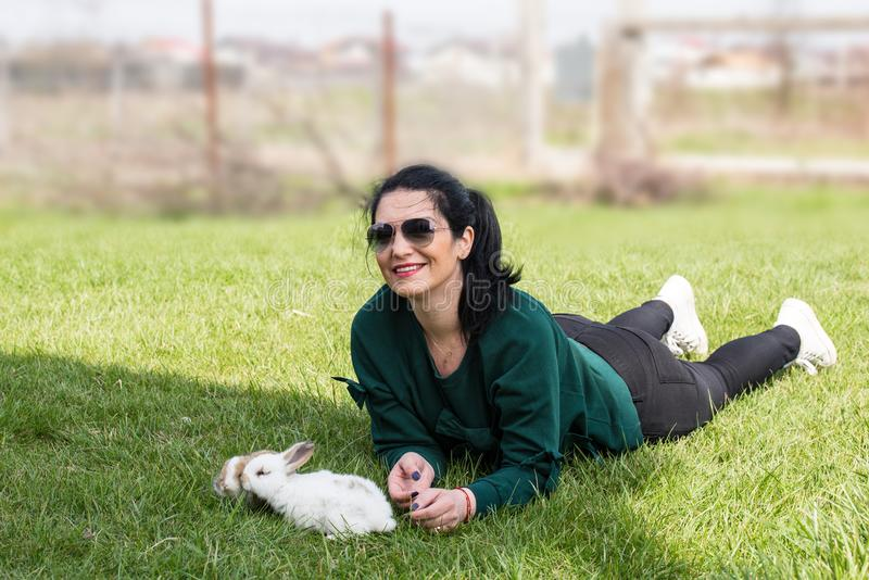 Woman laying on grass with bunnys. Woman laying on grass with little bunnys in spring sunny day royalty free stock photo