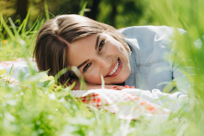 Woman laying in grass royalty free stock images