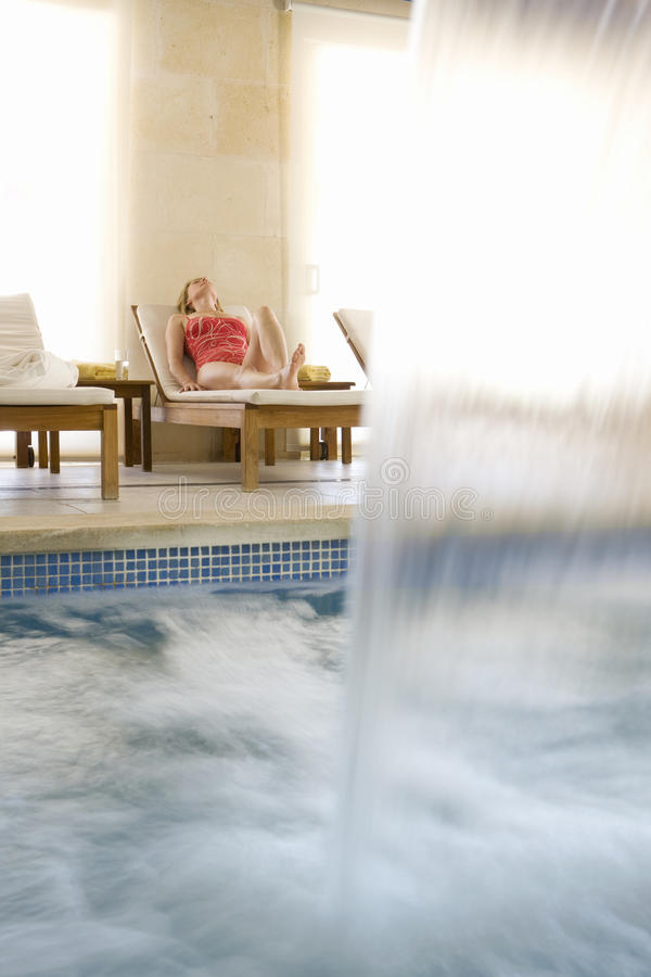 Woman laying on lounge chair near spa swimming pool with waterfall stock photos