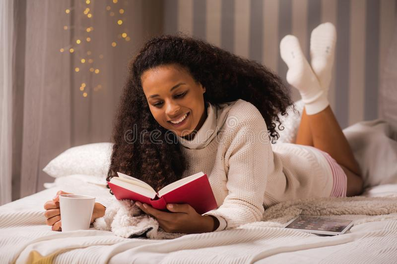 Woman laying with mug and book stock images