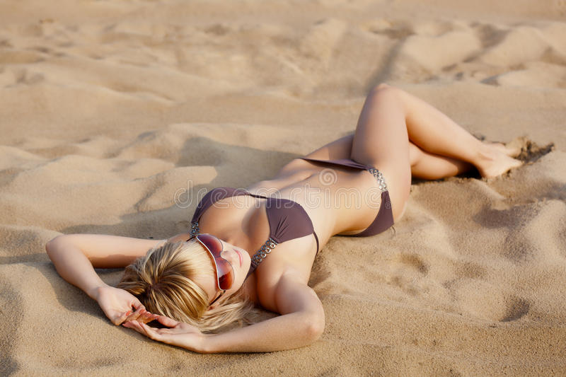 Woman laying on sand royalty free stock image