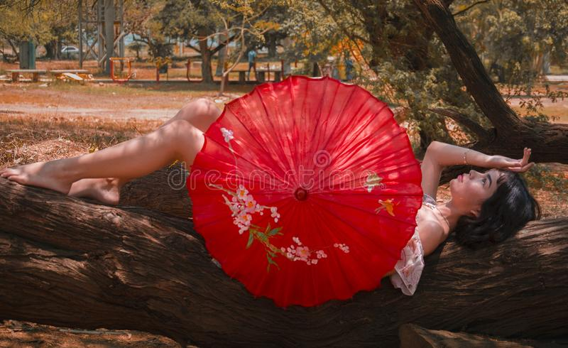 Woman Laying On Tree Log Holding Red Umbrella royalty free stock images