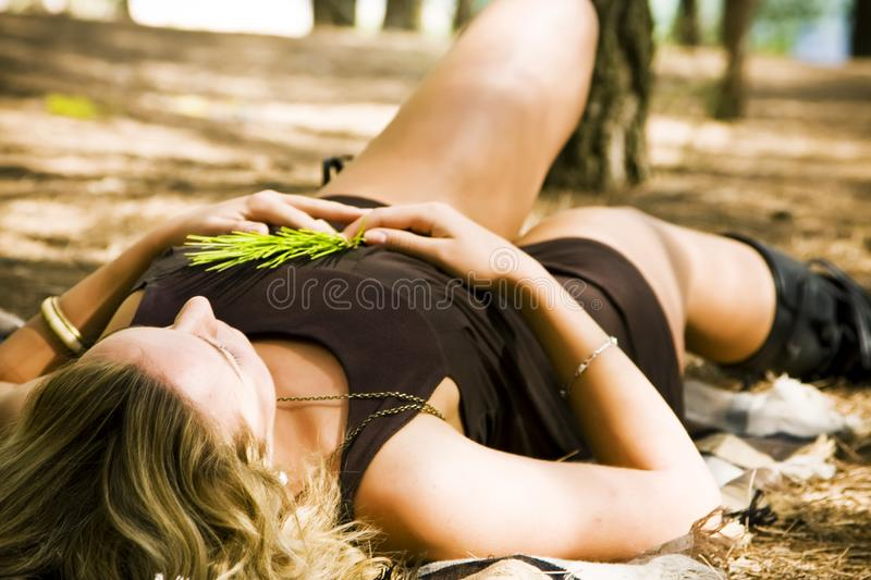 Woman laying in the woods royalty free stock images