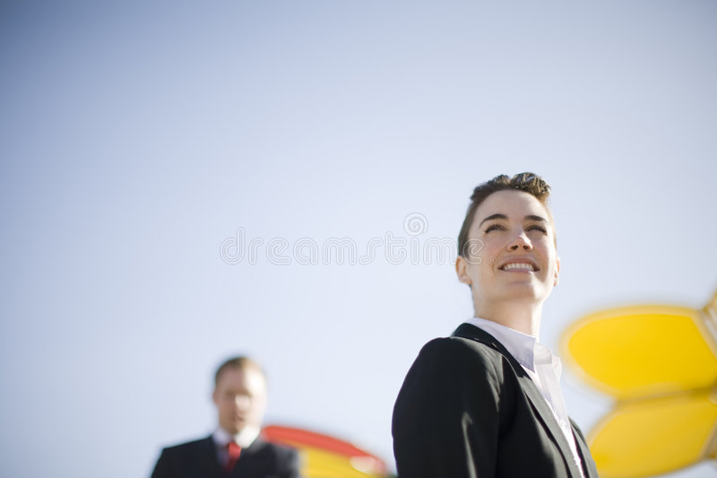 Woman leader. Close up of businesswoman standing looking away with businessman standing in background stock photos