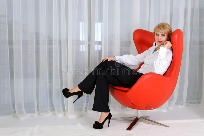 Woman, leader, who sits in a red chair. Concept of a confident business woman, leader, who sits in a red chair against a light background royalty free stock photography