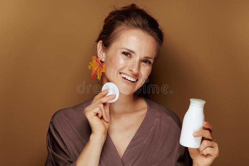 Woman with leaf earring using face cleansing milk and swab stock photo