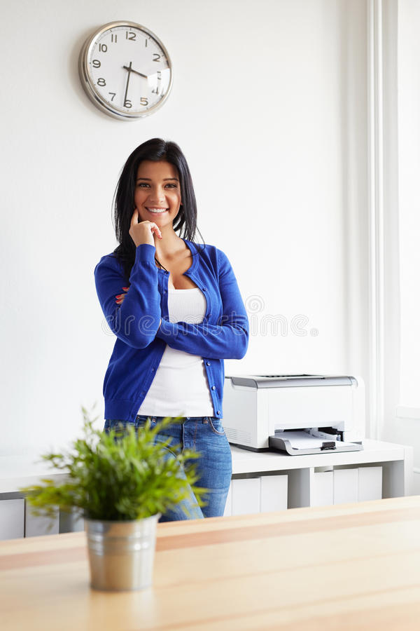 Woman leaning against a shelf in the office. Happy woman leaning against a shelf in the office royalty free stock photos
