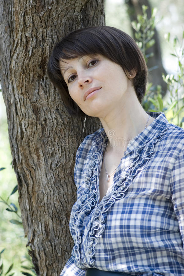 Download Woman leaning against tree stock image. Image of adult - 14366375