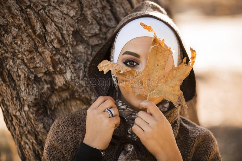 Woman Leaning on Brown Tree Holding Brown Leaf Covering Her Face stock photo