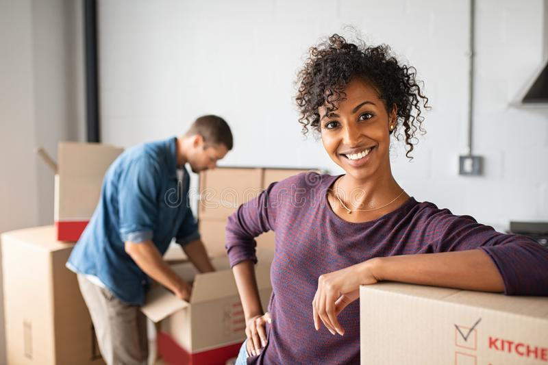 Woman leaning on cardboard box while moving house royalty free stock photo