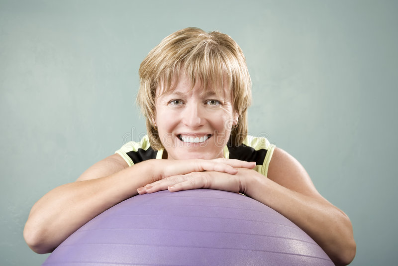 Woman Leaning on an Exercise Ball royalty free stock photos