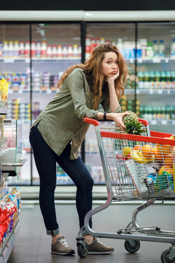 Woman leaning on a shopping cart at the supermarket royalty free stock photo