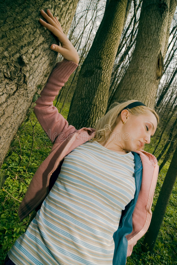 Woman leaning on tree trunk. stock photo