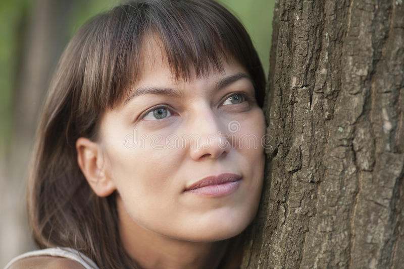 Woman Leaning On Tree Trunk. Closeup of thoughtful young woman leaning on tree trunk stock photos