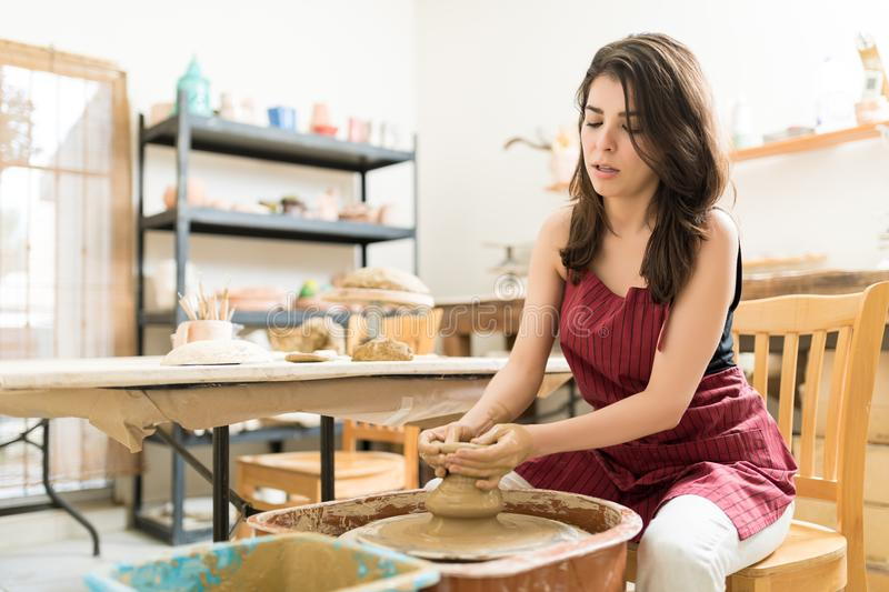 Woman Learning The Art Of Pottery In Studio. Beautiful mid adult woman learning the art of pottery in studio royalty free stock image