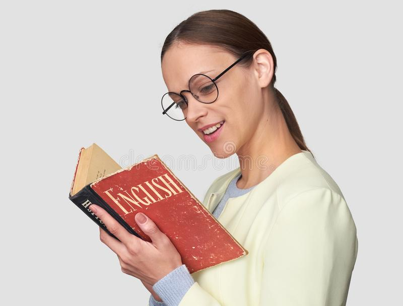 Woman learning foreign language. Girl reading an English textbook. Woman learning foreign language. Isolated stock photo