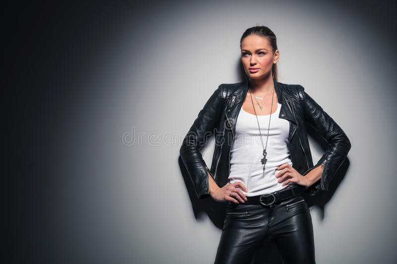 Woman in leather clothes with one hand behind her neck royalty free stock photos