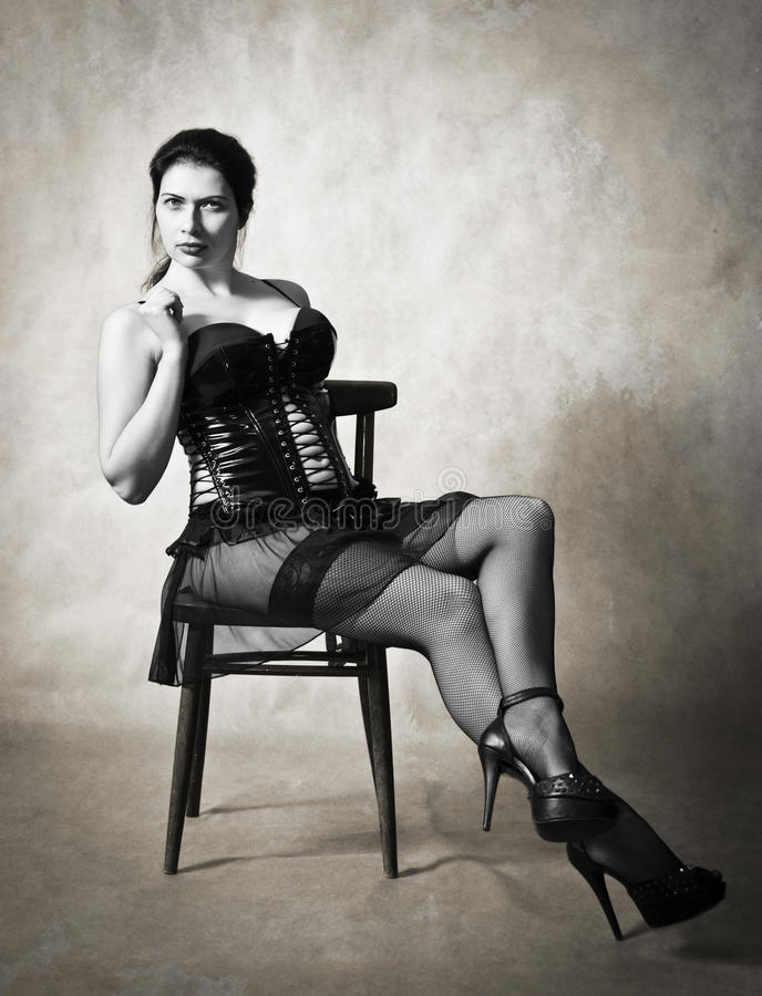 Woman in a leather corset and stockings on a chair royalty free stock photo