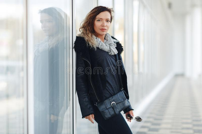 Woman in a leather jacket, black jeans posing in front of mirrored windows. Female fashion concept. Outdoor. white wall background stock images