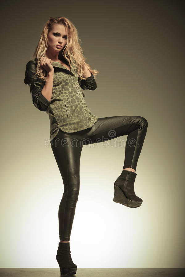 Woman in leather pants kicking and posing royalty free stock photos