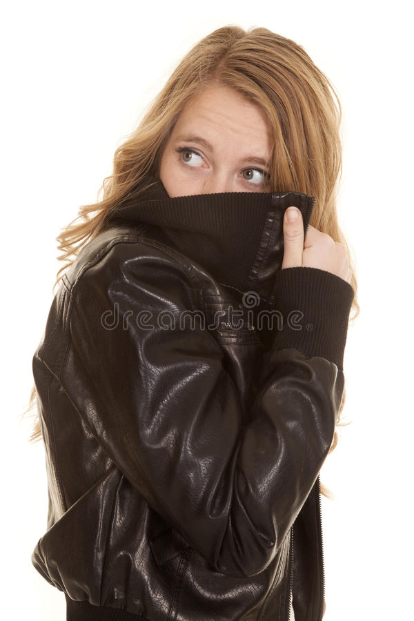Woman leather peek back behind jacket. A woman holding up her collar over her face stock photos