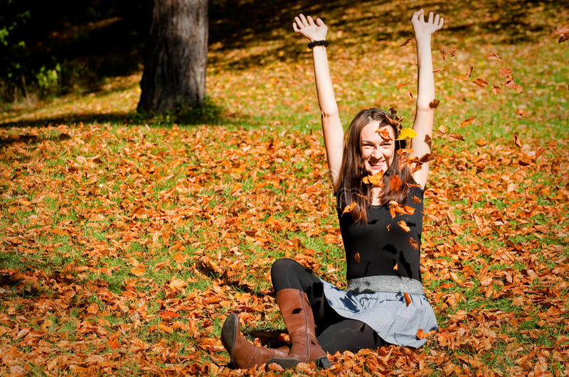 Woman on leaves. Beautiful woman playing with yellow leaves royalty free stock image