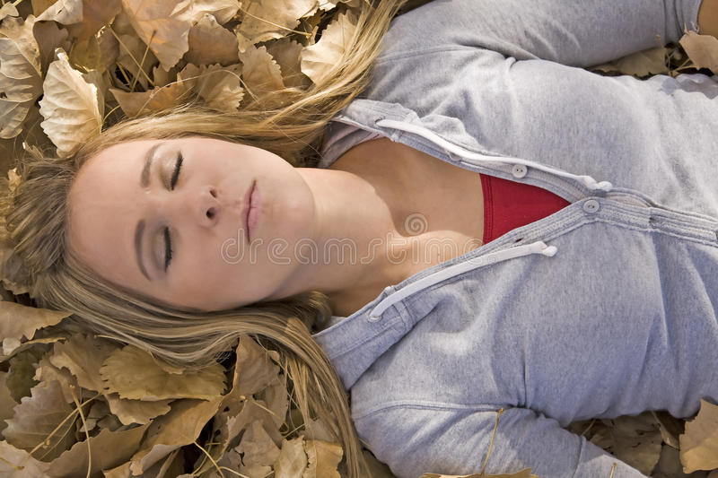 Woman in leaves eyes closed stock image