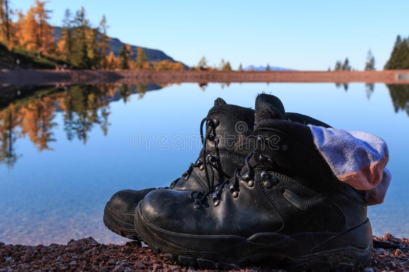 Hiking boots. Woman leaves hiking boots and socks next to a lake as she wades in water stock images