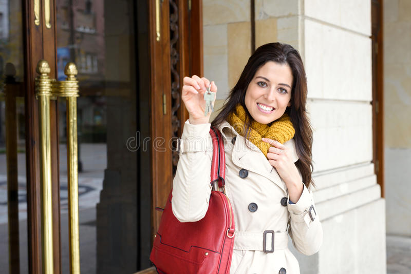 Woman leaving home and holding keys stock images