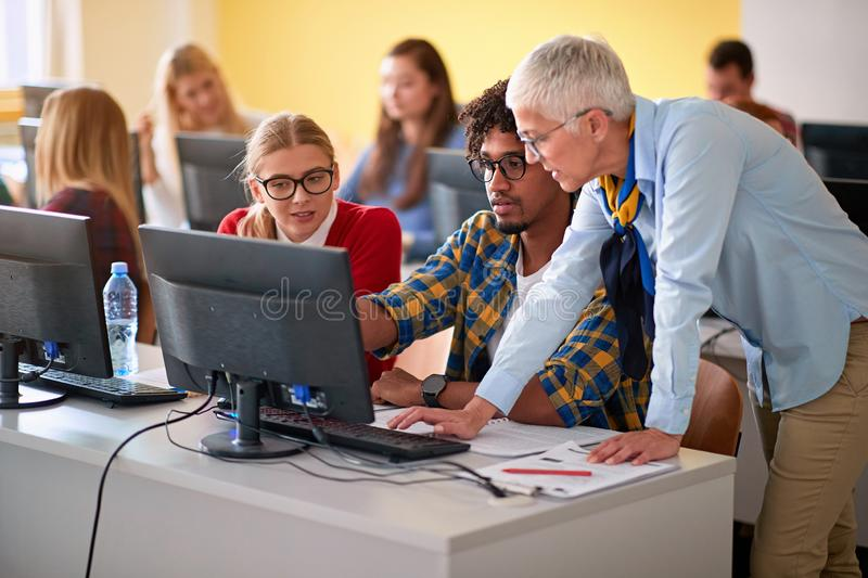 Woman lecturer in computer class assisting student on university stock photos