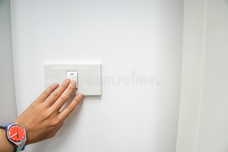 Woman left hand with cute watch turn off the office light switch for energy savings stock photo
